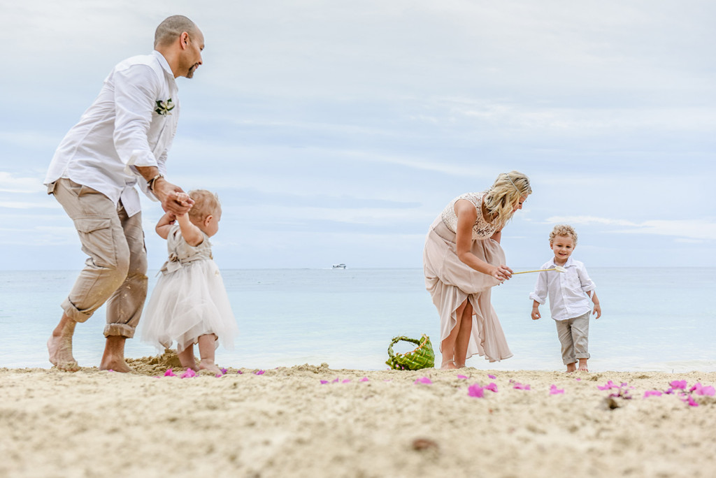 The wedded family plays on the shore at their family Beach Wedding on Malolo Island, Plantation Island hotel.