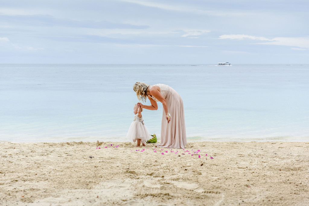 The bride soothes her daughter at the shore at their family Beach Wedding in Fiji.