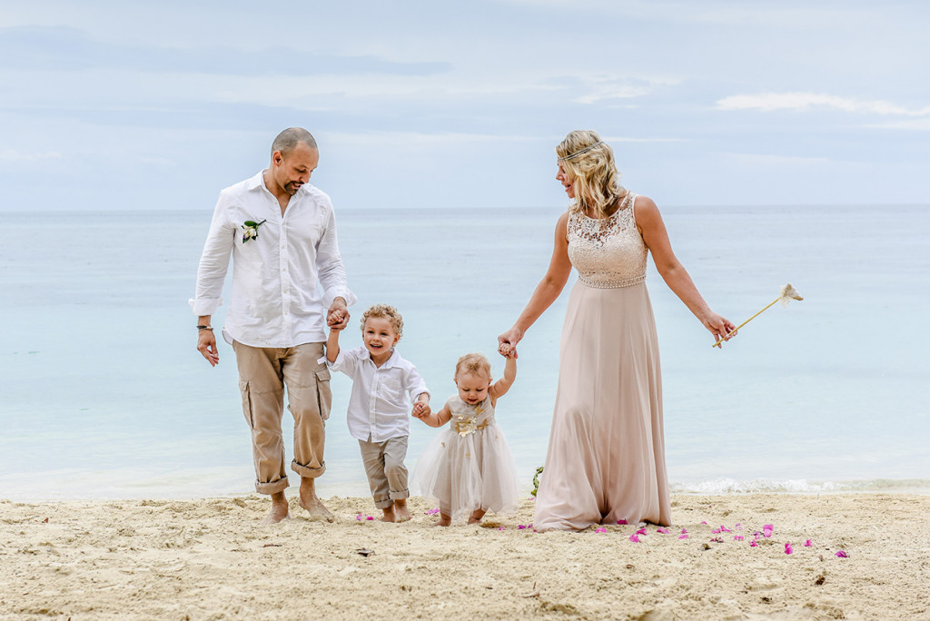 The couple pauses with their babies at their family Beach Wedding on Malolo Island, Fiji.