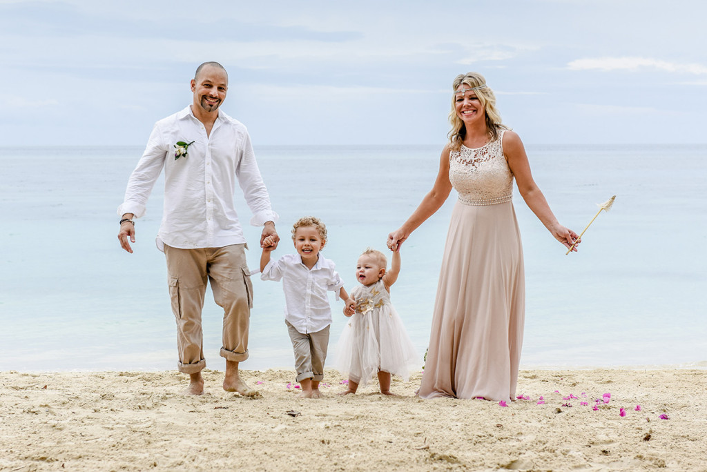 The couple walking with their children at their family Beach Wedding on Malolo Island, Plantation Island Resort, Fiji by Anais Photography.