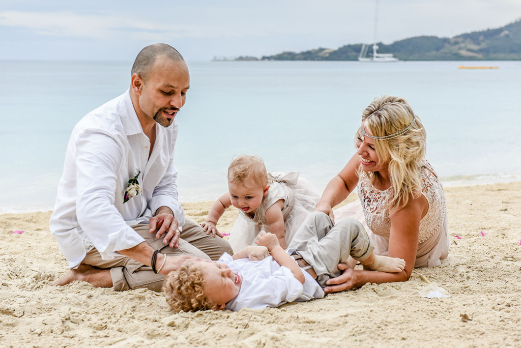 The couple play tickling with their children in the sand at their family Beach Wedding on Malolo Island, Plantation Island Resort, Fiji Wedding Photographer