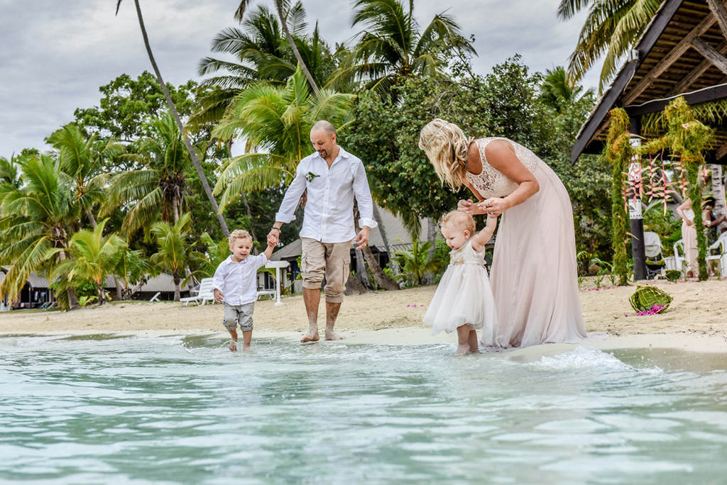The bride plays with her daughter on the shore at theri family Beach Wedding on Malolo Island, Plantation Island Resort, Fiji Wedding Photographer