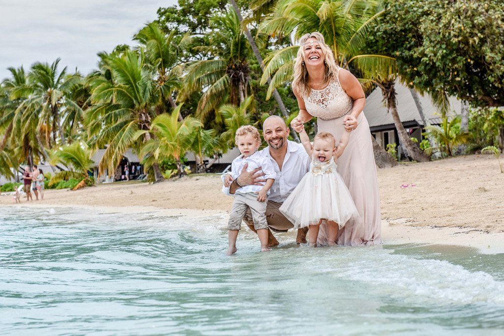 The couple pause with their babies in water at their family Beach Wedding on Malolo Island, Plantation Island Resort, Fiji Wedding Photographer