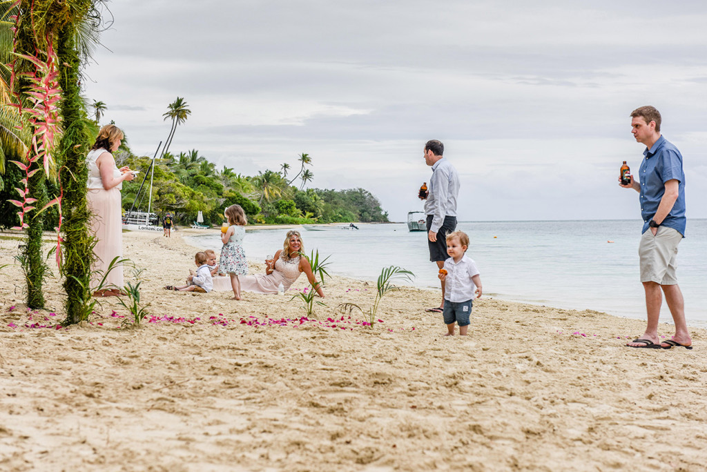 The couple, friends and their children relax on the beach at the family Beach Wedding on Malolo Island, Plantation Island Resort, Fiji Wedding Photographer