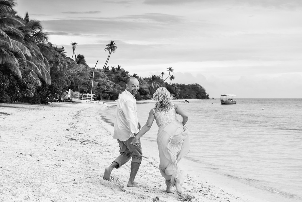 The couple runs hand-in-hand on the shores of the sea at their family Beach Wedding on Malolo Island, Plantation Island Resort, Fiji Wedding Photographer
