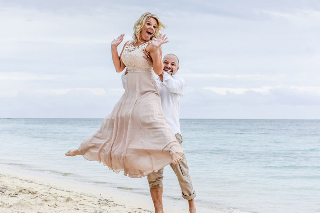 The groom lifts his bride on the shores of the sea at their family Beach Wedding on Malolo Island, Plantation Island Resort, Fiji Wedding Photographer
