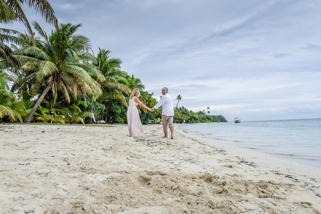 The Newly married couple walk hand in hand on the shores of the sea at their family Beach Wedding on Malolo Island, Plantation Island Resort, Fiji Wedding Photographer