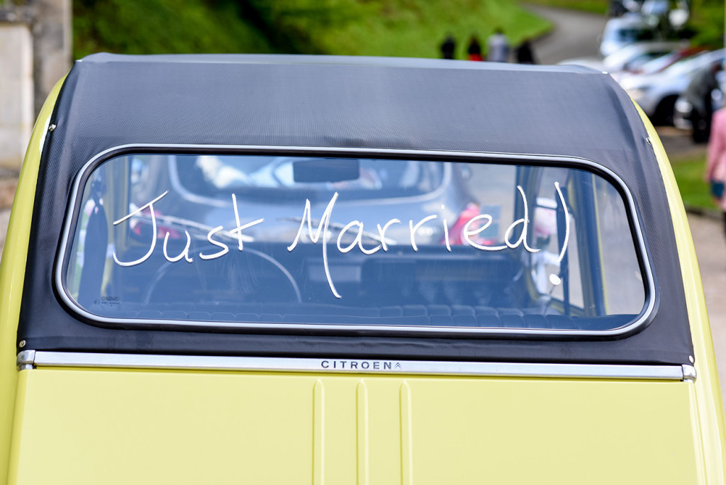 Just married on the back of the yellow vintage car