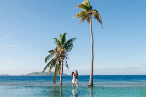 Couple cuddling by the pool between palm trees with ocean in the background at Mana Island resort, Fiji by Anais Photography