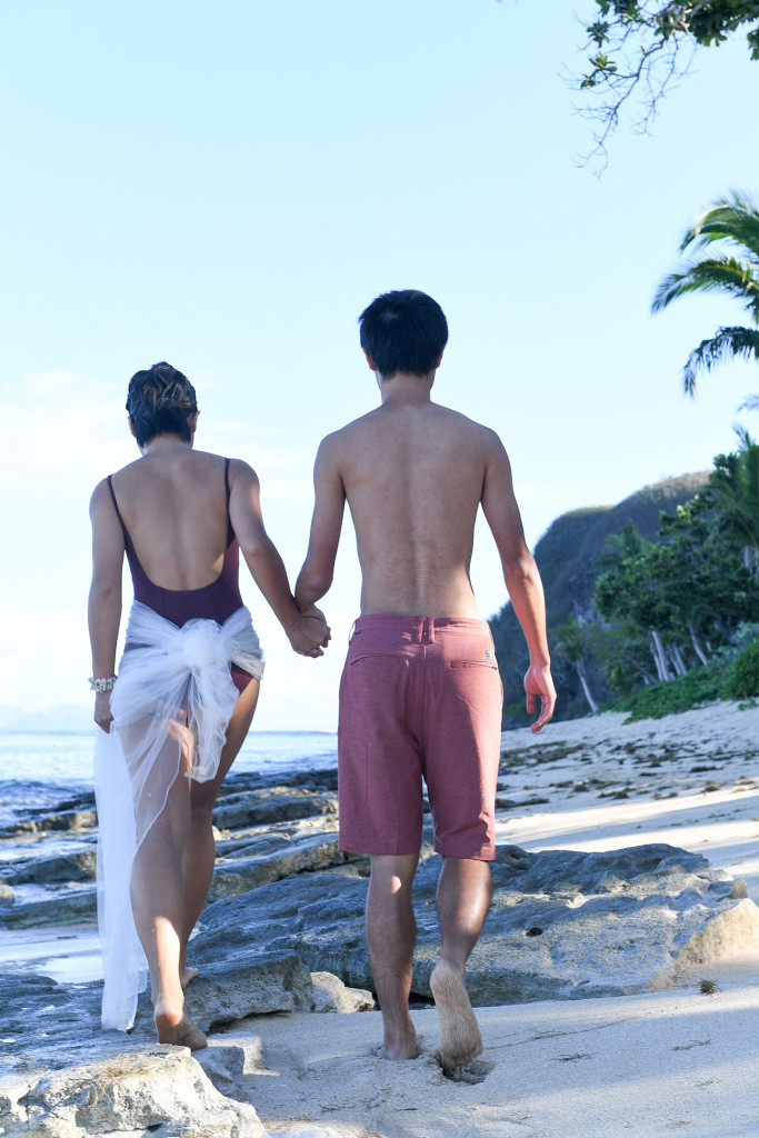 couple holding hands wearing swimwear at Tokoriki island resort in Fiji photographed by Anais Photography