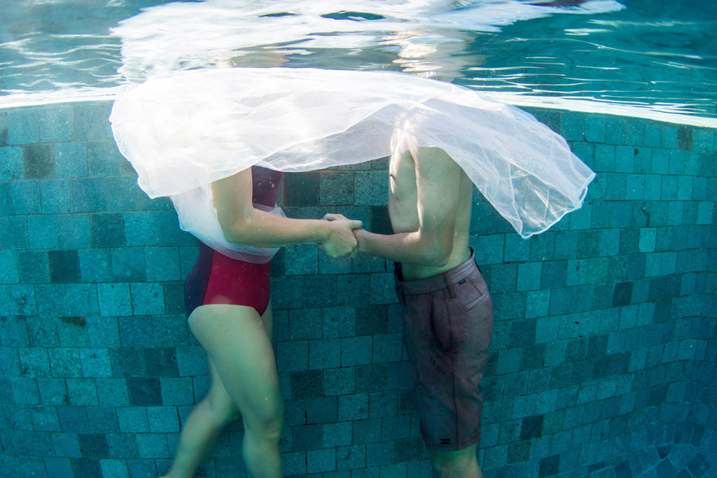underwater couple holding hands in the swimming pool at Tokoriki island resort in Fiji photographed by Anais Photography