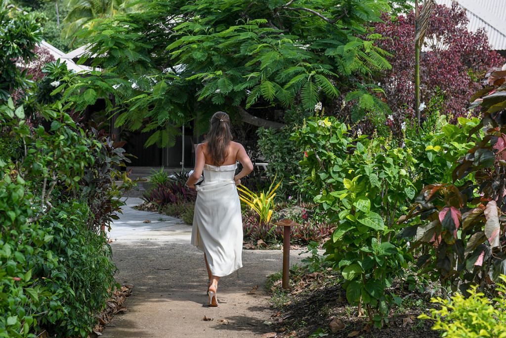 Mother is walking to the ceremony holding her dress at Vomo Island resort, Fiji