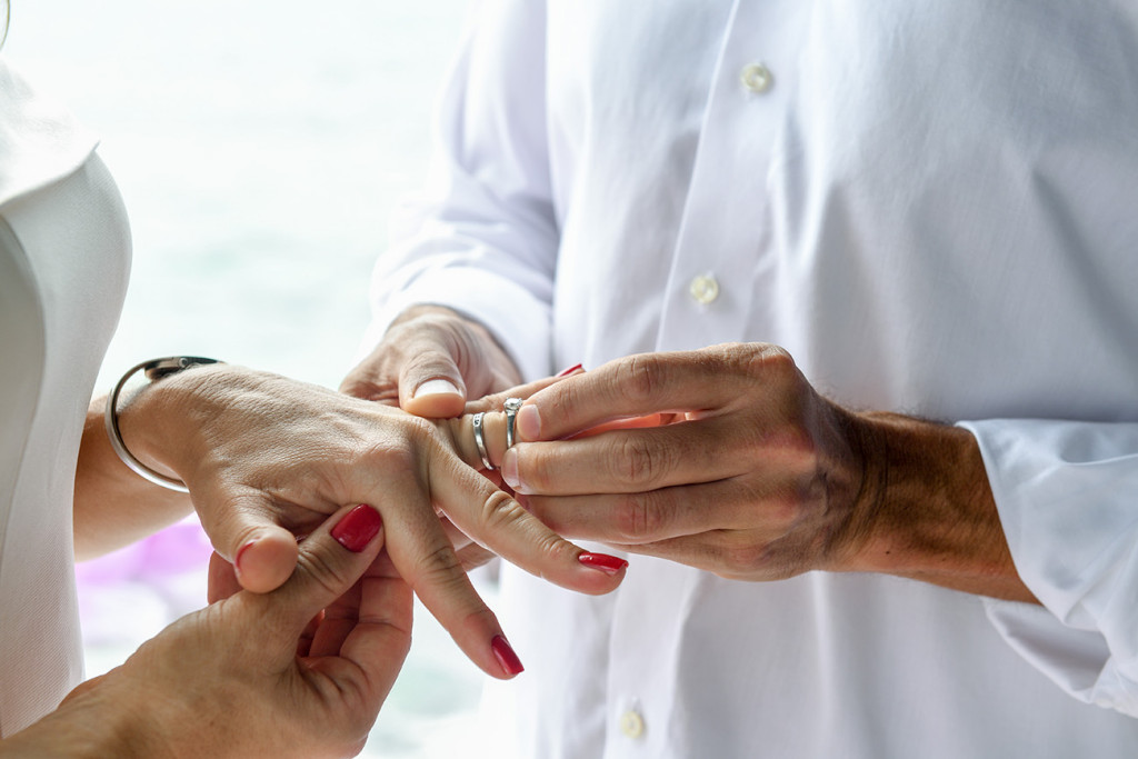 Husband is putting the ring on his wife's finger at the ceremony at Vomo Island resort, Fiji