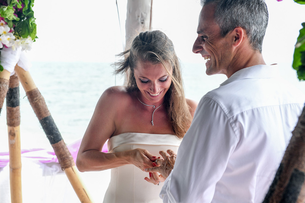 The wife is trying to put the wedding ring on her husband's finger at Vomo Island resort, Fiji