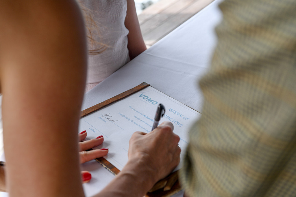 The wife is signing her renewal of vows certificate at Vomo Island resort, Fiji