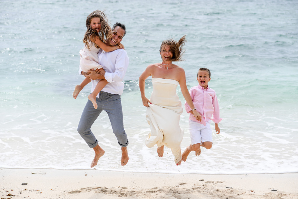 Family jumping by the beach at Vomo Island resort, Fiji