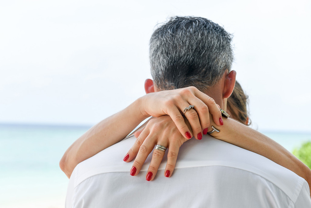 The wife's hands are holding her husband's neck at Vomo Island resort, Fiji