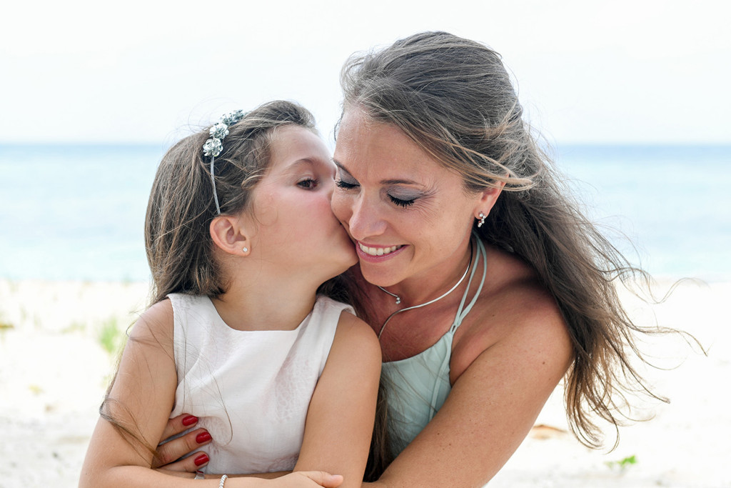 Daughter kissing her mother at Vomo Island resort, Fiji