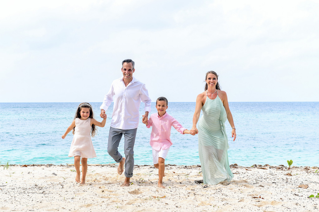 Family walking along the beach at Vomo Island resort, Fiji