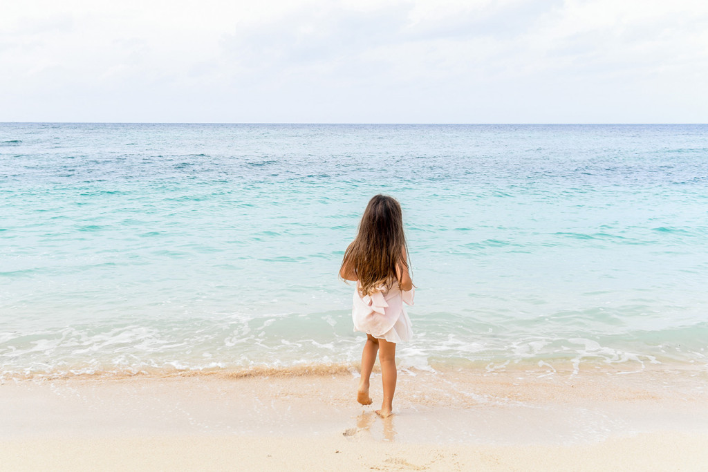 Young girl walking toward the blue sea at Vomo Island resort, Fiji