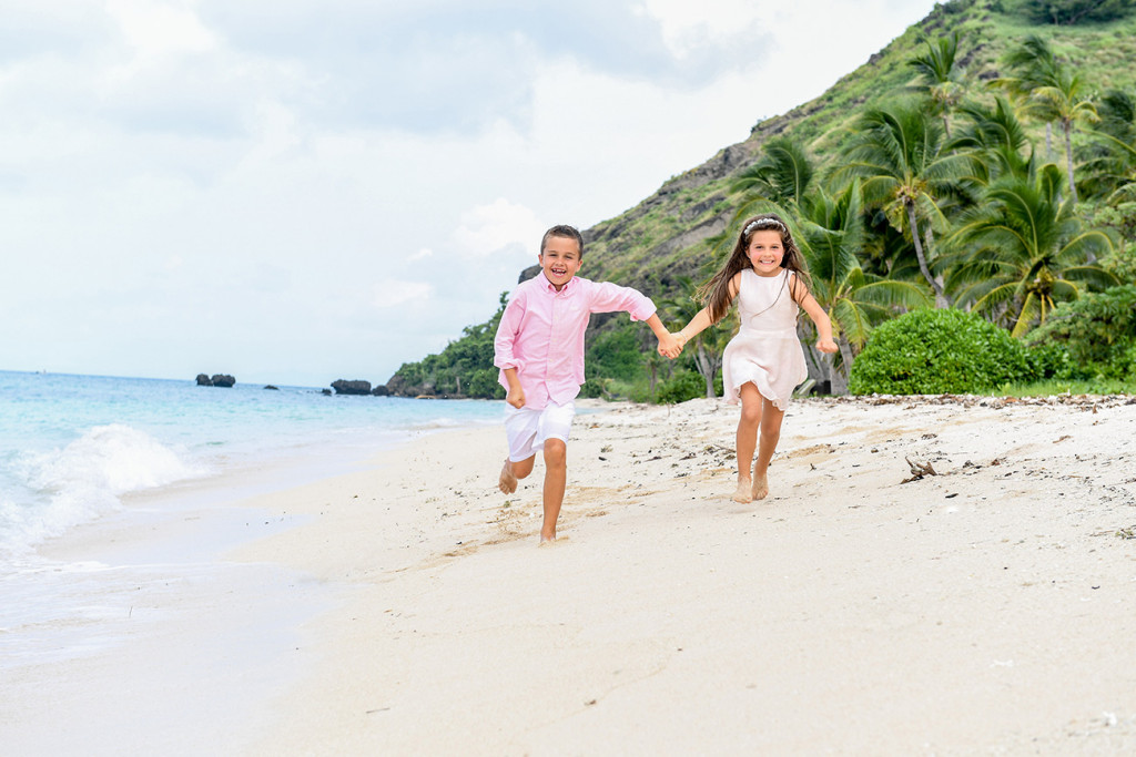 Brother and sister are running along the beach at Vomo Island resort, Fiji