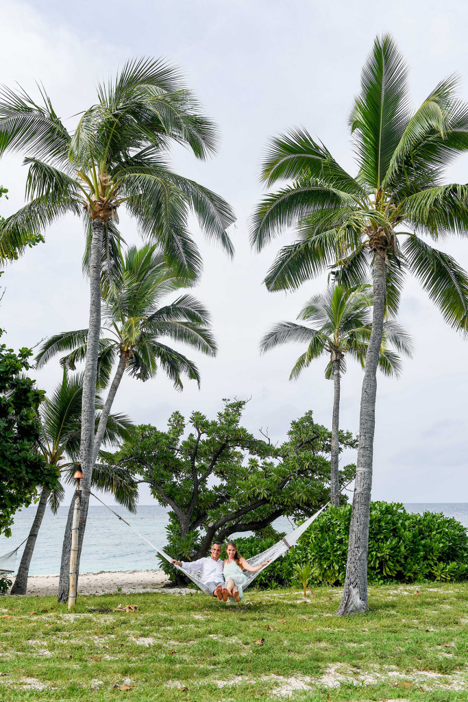 Couple on hammoc between two palm trees at Vomo Island resort, Fiji