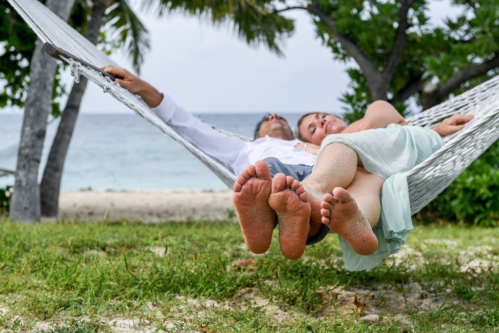 Couple on hammock lying with sea in the background at Vomo Island resort, Fiji