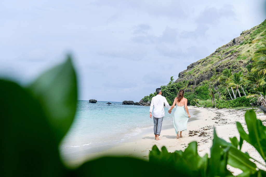 Couple walking along the beach at Vomo Island resort, Fiji