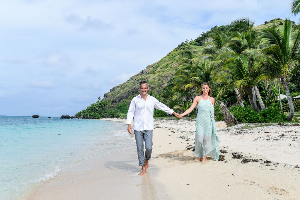 Couple walking along the beach and holding hands for their 10 years wedding anniversary at Vomo Island resort, Fiji