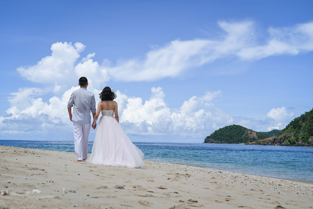 Bride and groom walking along the beach at Paradise Cove island resort, Fiji
