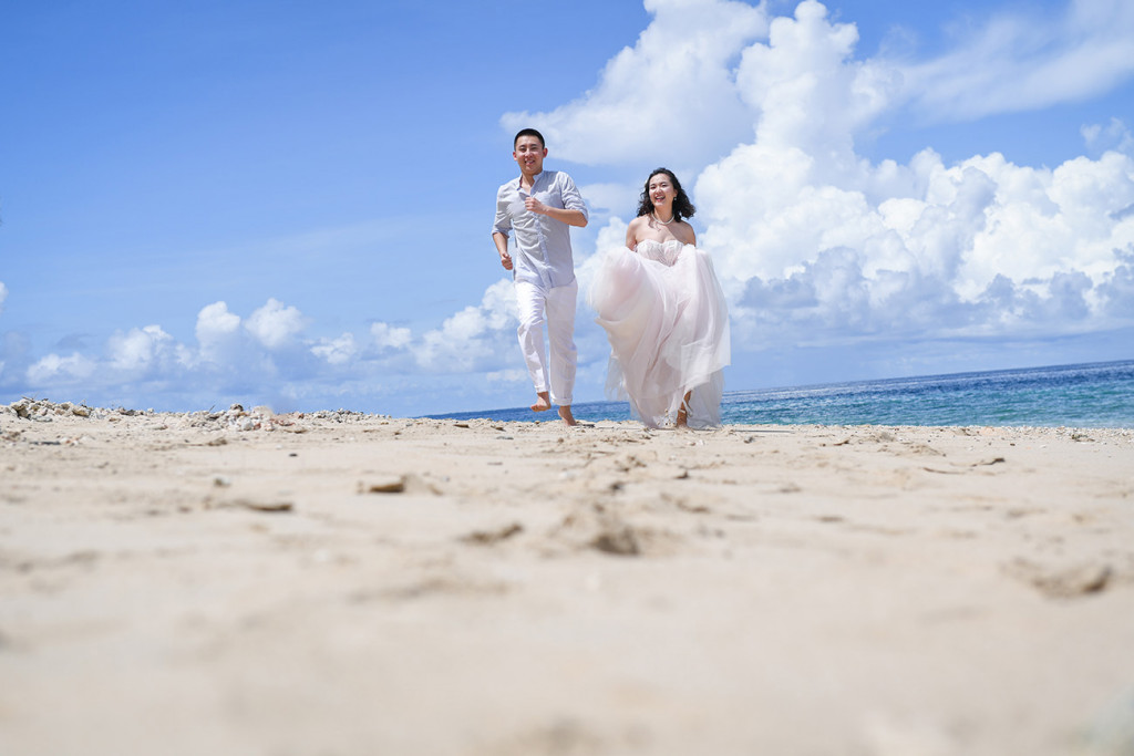 Bride and groom are running along the beach and its white sand at Paradise Cove island resort, Fiji