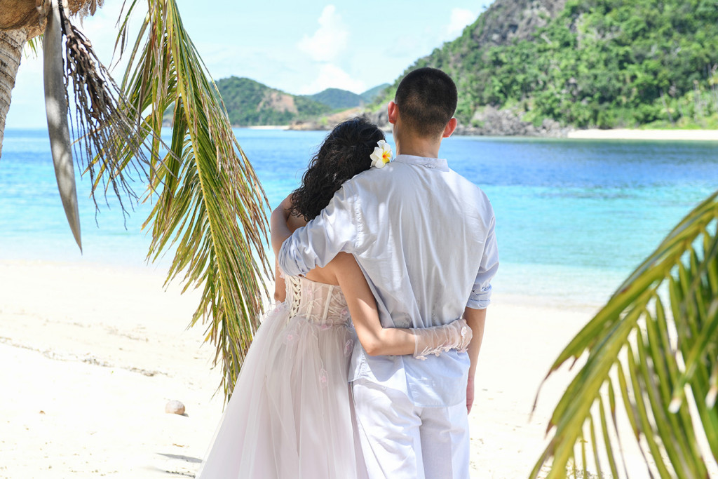 Back of bride and groom watching at the sea Paradise Cove island resort, Fiji