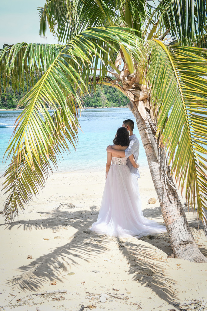 Bride and groom in the shade of a palm tree Paradise Cove island resort, Fiji