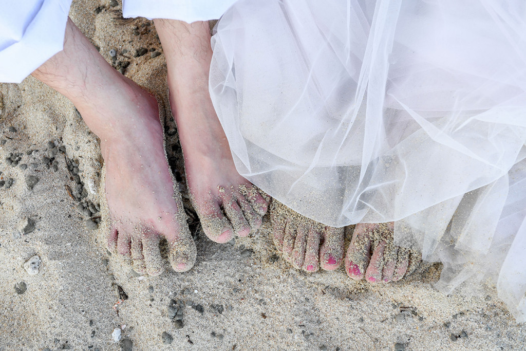 The couple's feet in the white sand Paradise Cove island resort, Fiji