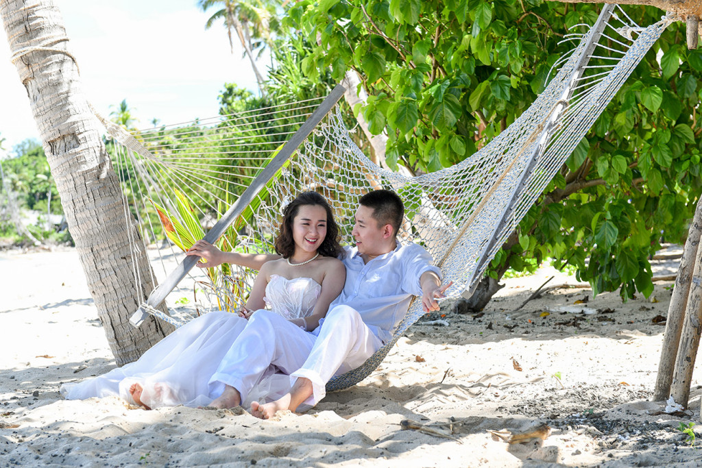 The couple is lying down in a hammock in the beach Paradise Cove island resort, Fiji