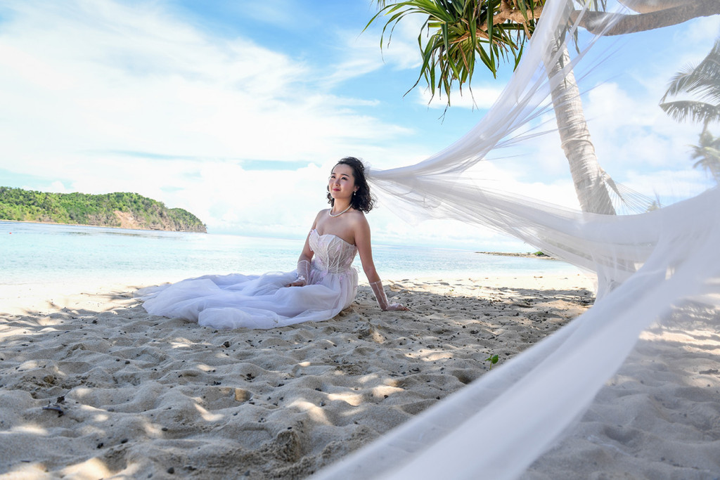 Bride sitting at the beach with her veil coming to the lens Paradise Cove island resort, Fiji