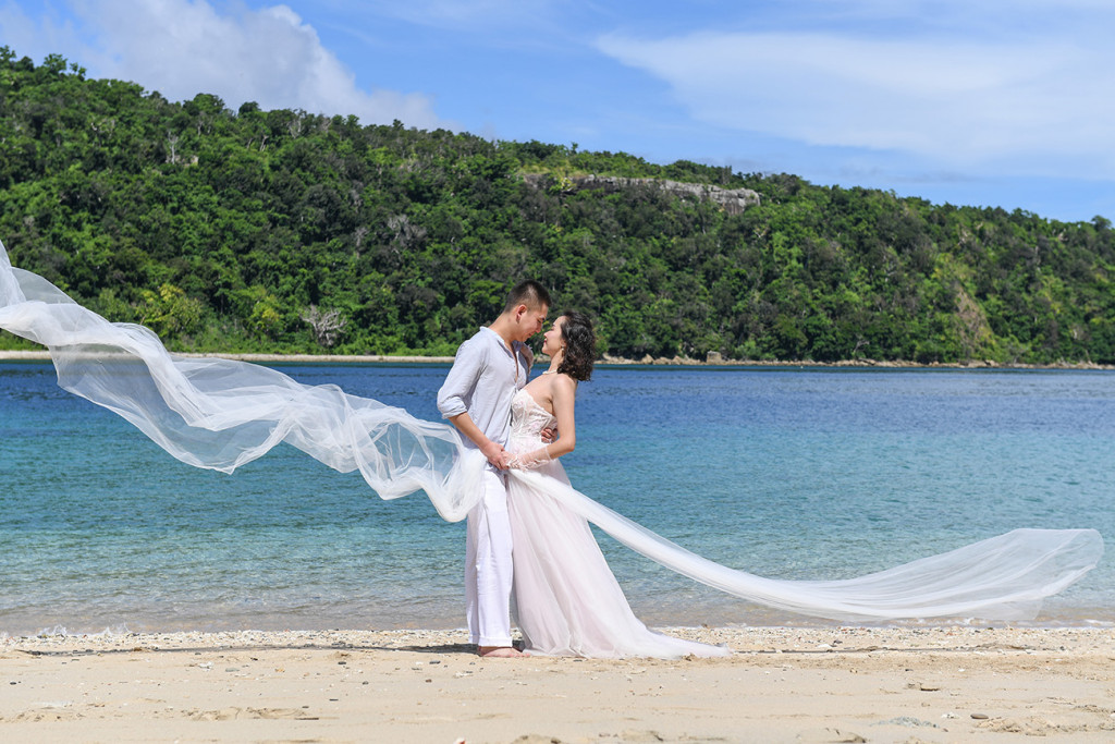 the bride and groom are holding eachothers while the veil is falling around them Paradise Cove island resort, Fiji