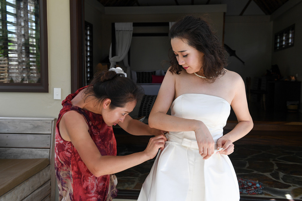 The bride is having help to put her wedding skirt on at Paradise cove island resort, Yasawas, Fiji