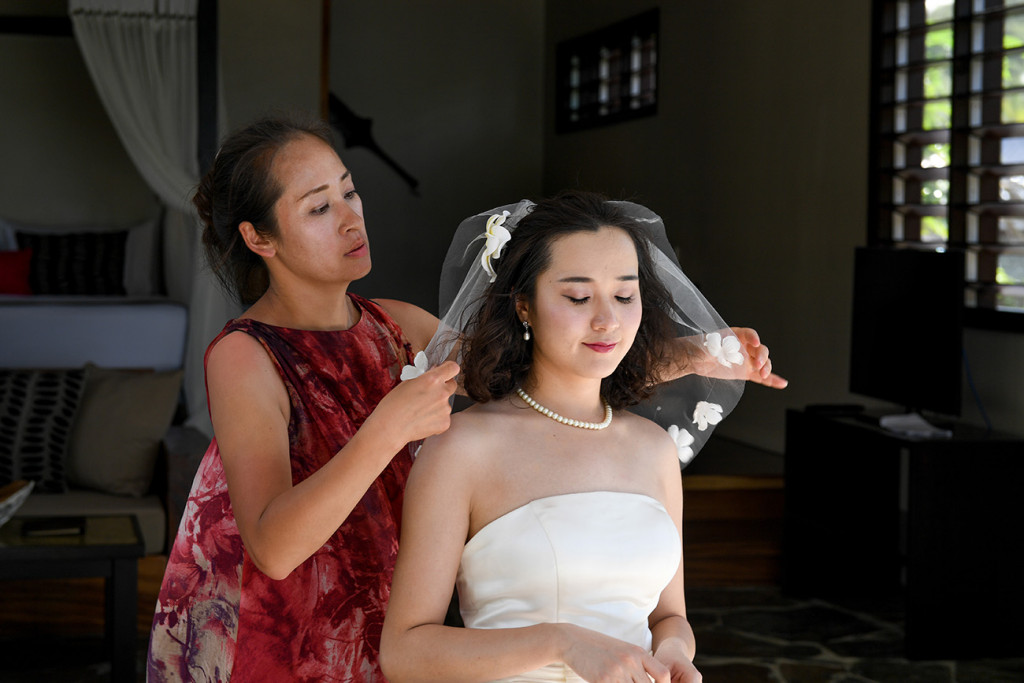 The bride's friend is helping her to put on her veil at Paradise cove island resort, Yasawas, Fiji