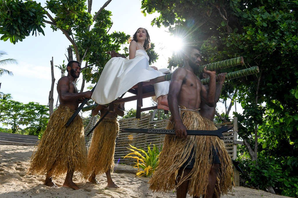 The Fijian warriors are carrying the bride to the wedding ceremony at Paradise cove island resort, Yasawas, Fiji