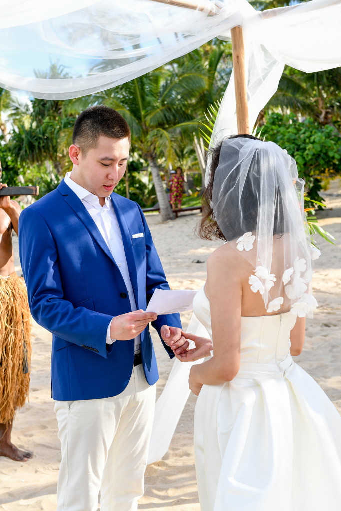 The groom is telling the bride his vows at Paradise cove island resort, Yasawas, Fiji