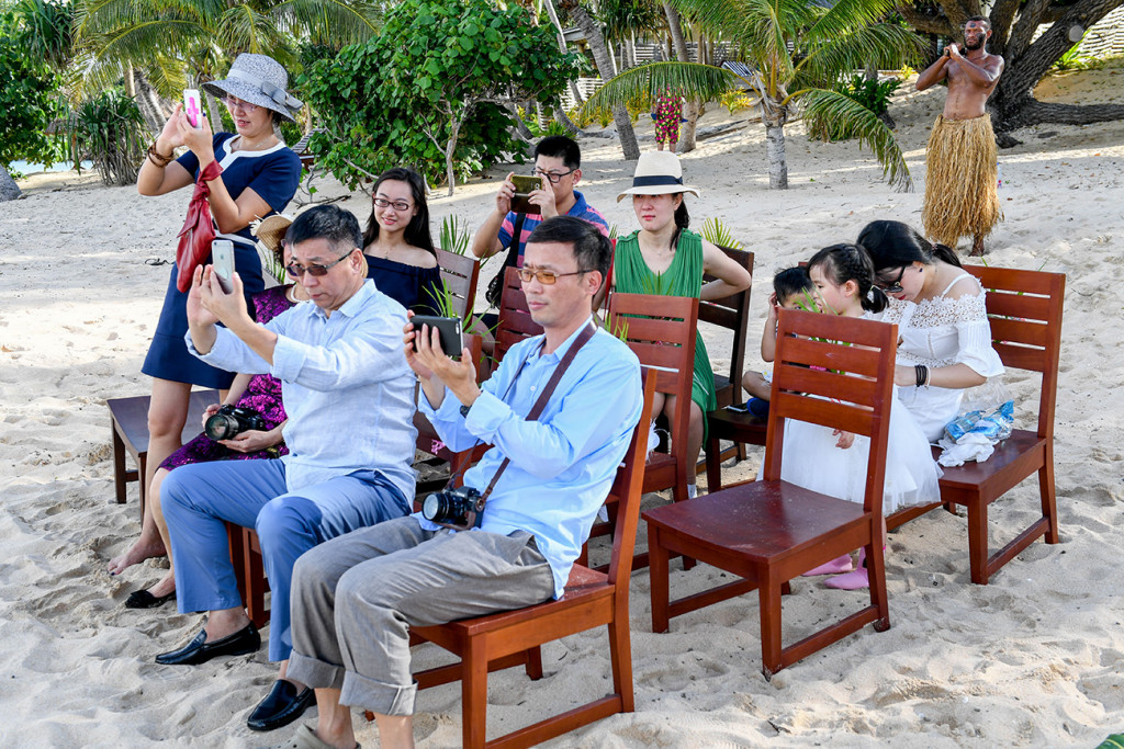 The guests are taking photos during the wedding ceremony at Paradise cove island resort, Yasawas, Fiji