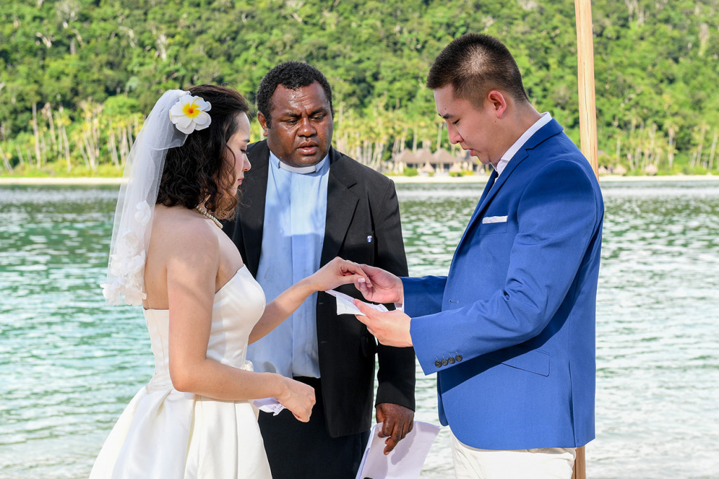 The groom is putting the ring on his wife's finger at Paradise cove island resort, Yasawas, Fiji
