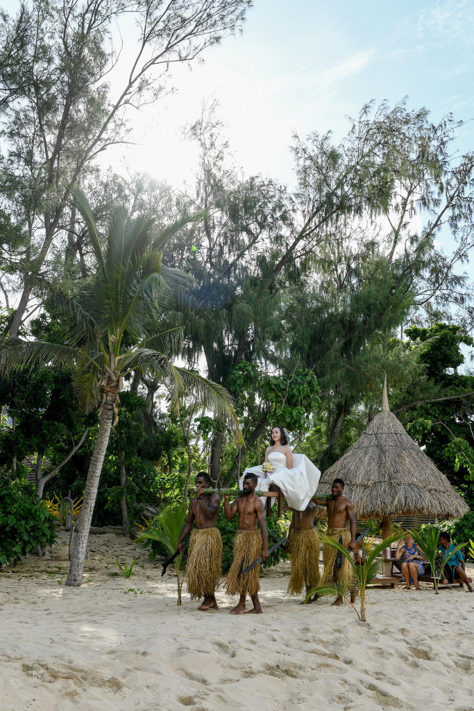 The bride is carried by the Fijian warriors to the beach at Paradise cove island resort, Yasawas, Fiji