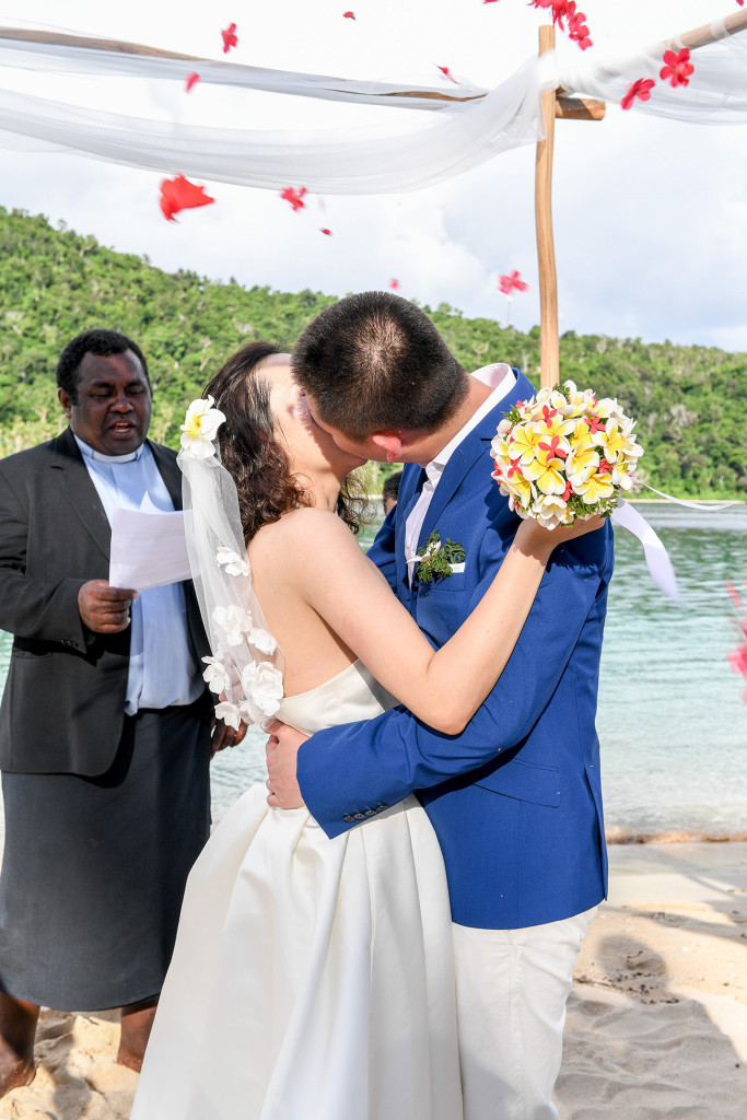 The bride and groom are kissing and the petals are thrown at them at Paradise cove island resort, Yasawas, Fiji