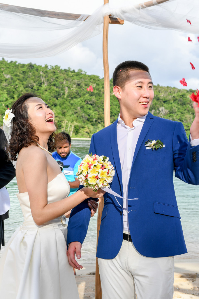 Petals are flying above the husband and wife after their wedding ceremony at Paradise cove island resort, Yasawas, Fiji