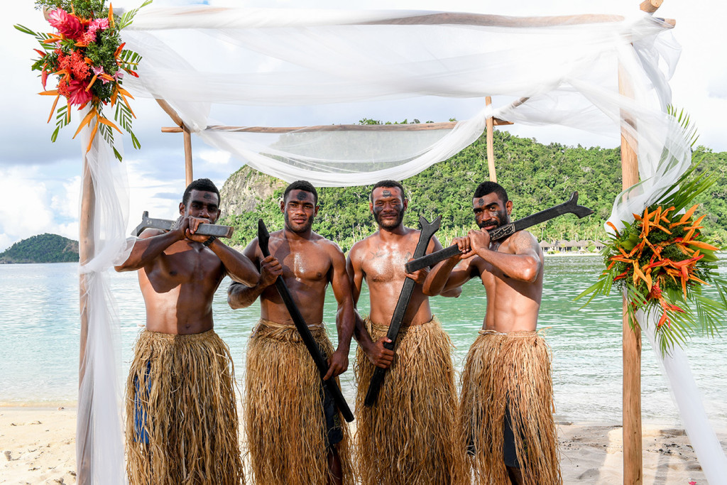 Four fijian warriors posing by the beach at Paradise cove island resort, Yasawas, Fiji