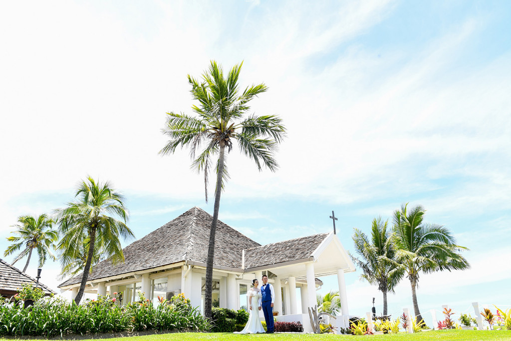 The bride and the groom are posing by the chapel at the sheraton beach in Denerau, Fiji
