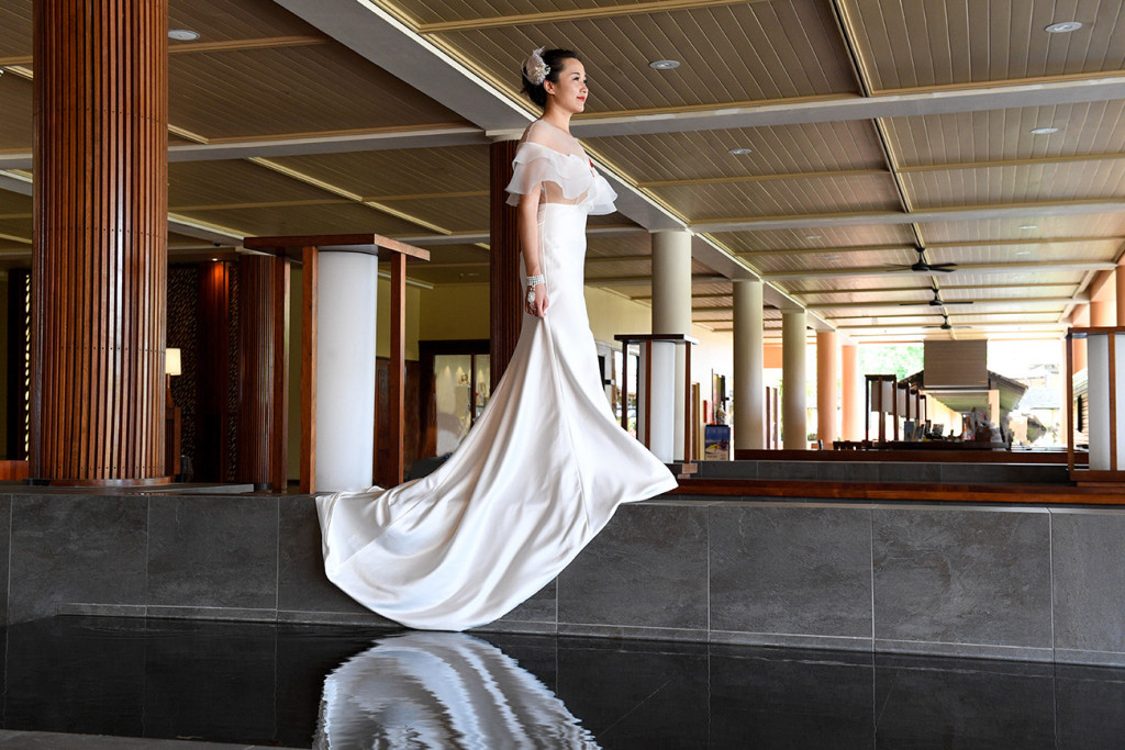 The bride is walking above a pond at the reception hall of the Sheraton resort in Denerau