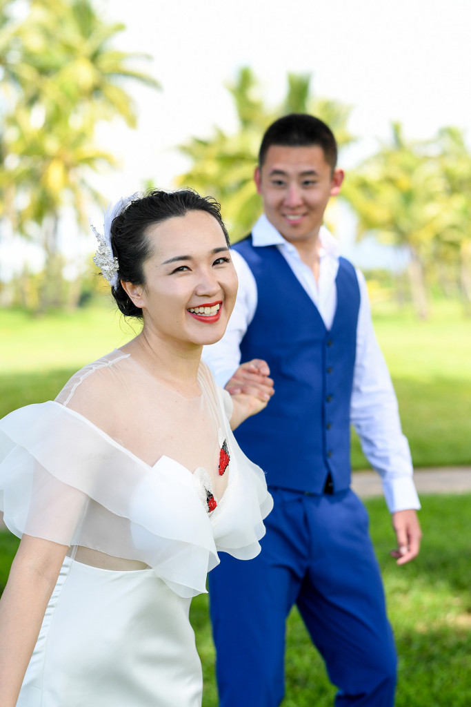 Portrait of the bride while her husband is pulling her in the back at the golf course in Denerau, Nadi Fiji.